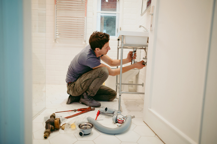 man working on plumbing under sink